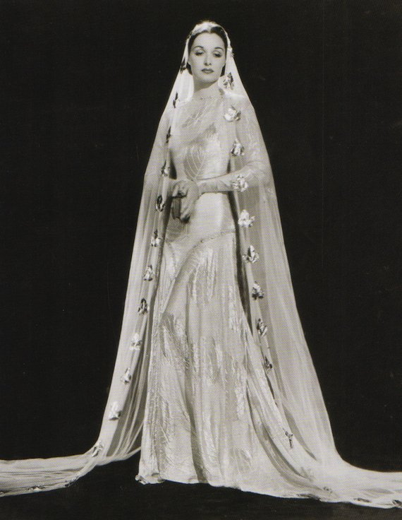 1930s fashion portrait, Wedding dress in bias cut silk with large self coloured leaf design in contrast texture. The veil is decorated with gold rosettes.